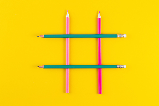1125605742 istock photo Hashtag sign from crossed colorful pencils on yellow background. 1257940591