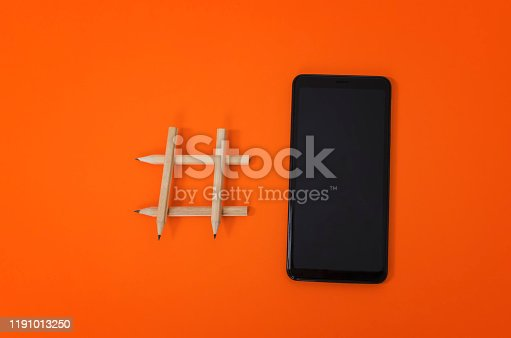 1125605742istockphoto Hashtag sign made of pencil and smartphone 1191013250