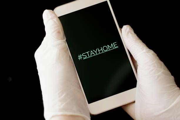 Hashtag stay home! The inscription on the smartphone screen. Female hand in a white glove holds a phone. The recommendation is quarantined at home to prevent coronovirus covid 19. stock photo
