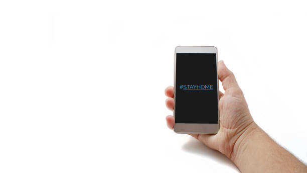 Hashtag stay home! The inscription on the smartphone screen. Male hand holds a phone isolated on a white background. The recommendation is quarantined at home to prevent coronovirus covid 19. stock photo