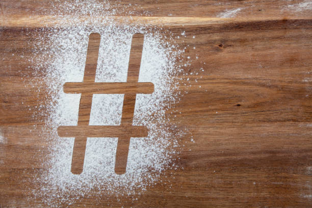 Hashtag symbol stencil in flour on a wooden board stock photo