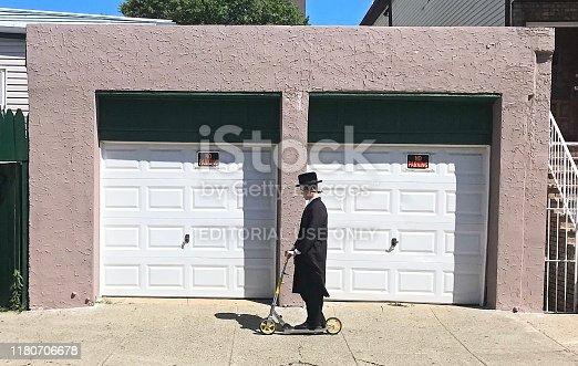 New York City, USA - June 26, 2019: Hasidic Jew man riding on a kick scooter on sidewalk in Brooklyn.
