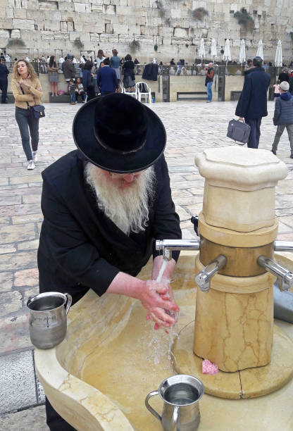 Hasidic Jew washing his hands before praying at the Holy Western Wall. stock photo