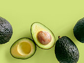 Fresh organic hass avocados on a green background, top view with copy space