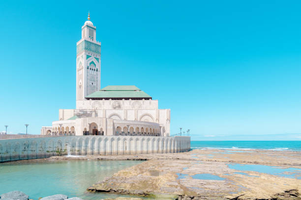 Hassan II Mosque in Casablanca on the blue cloudless sky and ocean background. stock photo