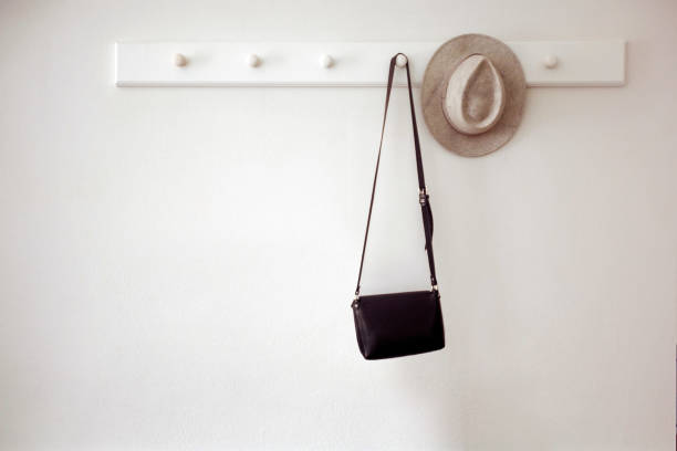 Hat and bag hanging on pegs Stylish hat and small black purse hanging on white pegs on wall in cozy room coathanger stock pictures, royalty-free photos & images