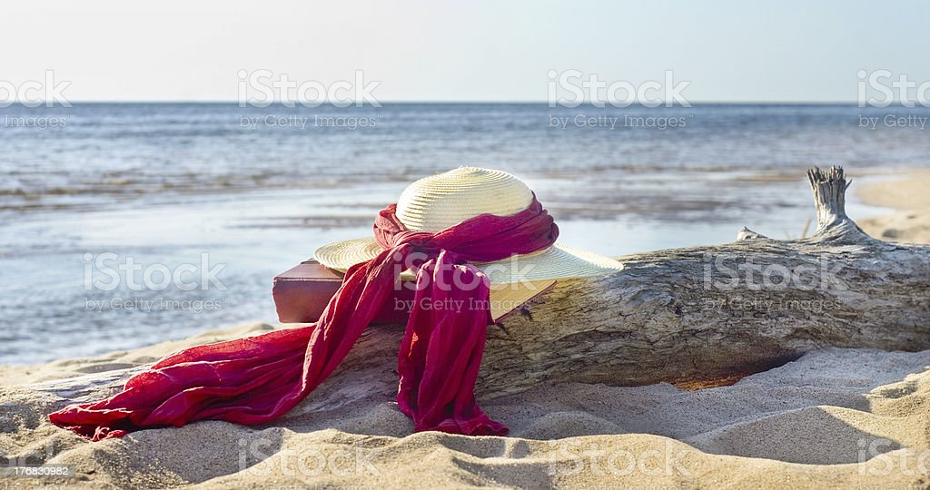 Hat and book on seacoast royalty-free stock photo