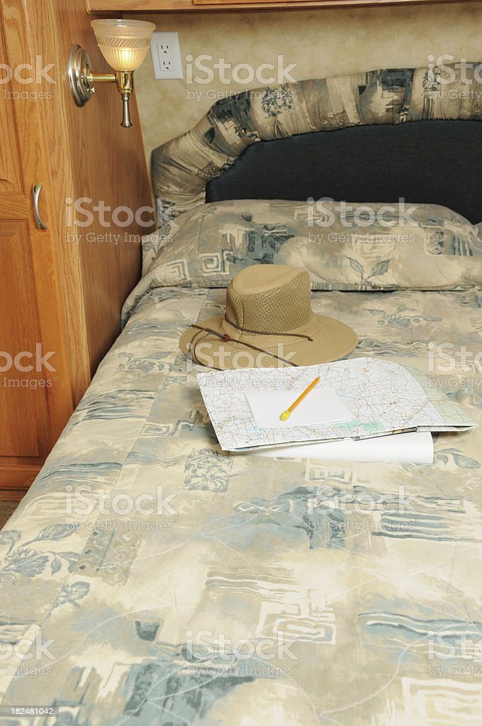 Hat and map on RV bed royalty-free stock photo