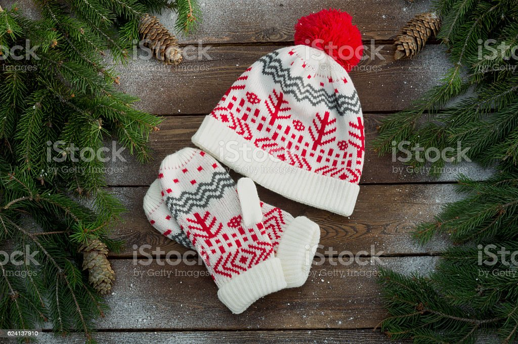 hat and mittens on a wooden background with Christmas trees stock photo