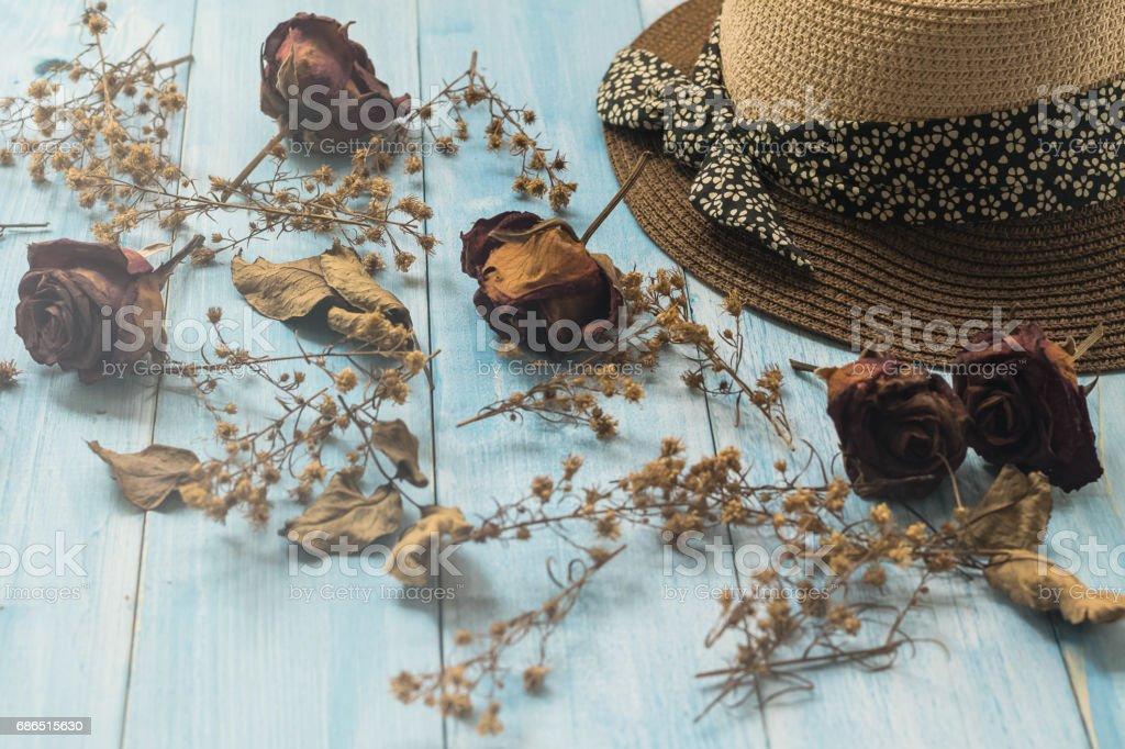 Hat and rose dry flower on blue wood background zbiór zdjęć royalty-free