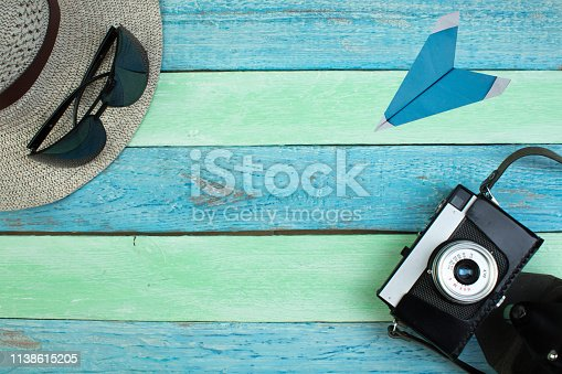 Hat, camera, bag, glasses, sunscreen on a summer wooden background. Top view and copy space