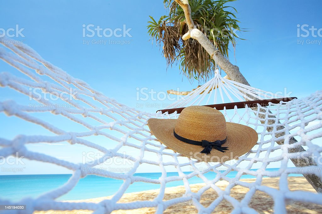 A hat resting on a hammock under a palm tree on a beach stock photo
