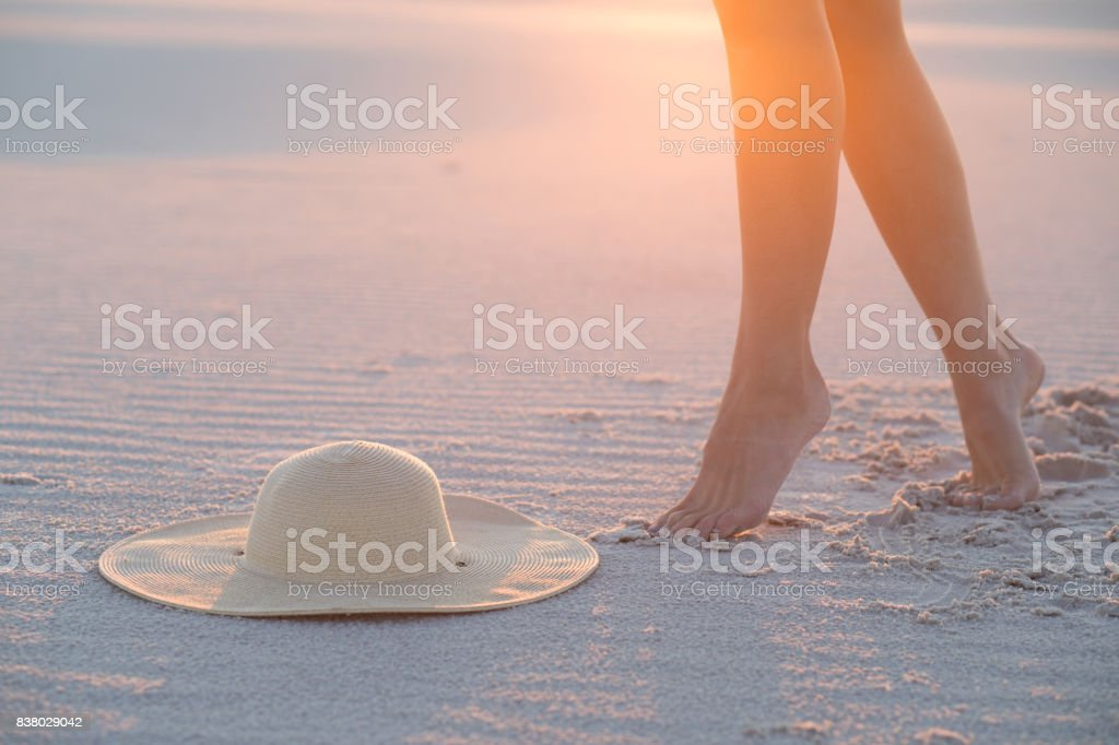 Cтоковое фото Hat, sand and female legs. Beach holidays concept.