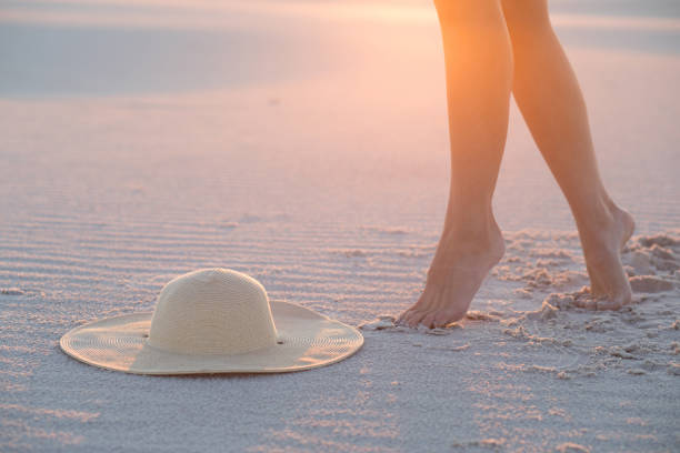 Hat, sand and female legs. Beach holidays concept. – zdjęcie
