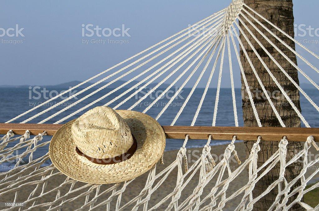 Hat sitting on a hammock near the beach royalty-free stock photo