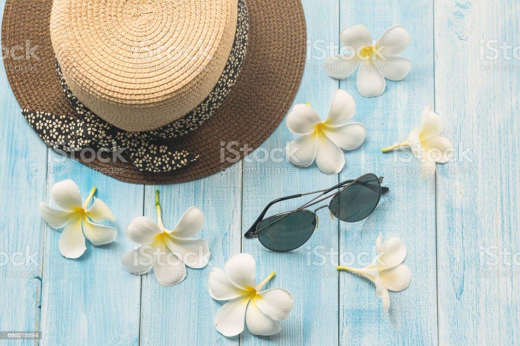 Hoed, zonnebril en rose droge bloem op blauwe houten achtergrond royalty free stockfoto