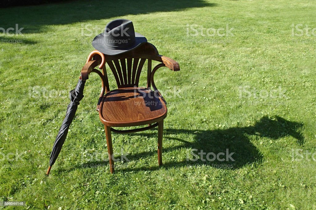 Hat, umbrella and a chair on the grass stock photo