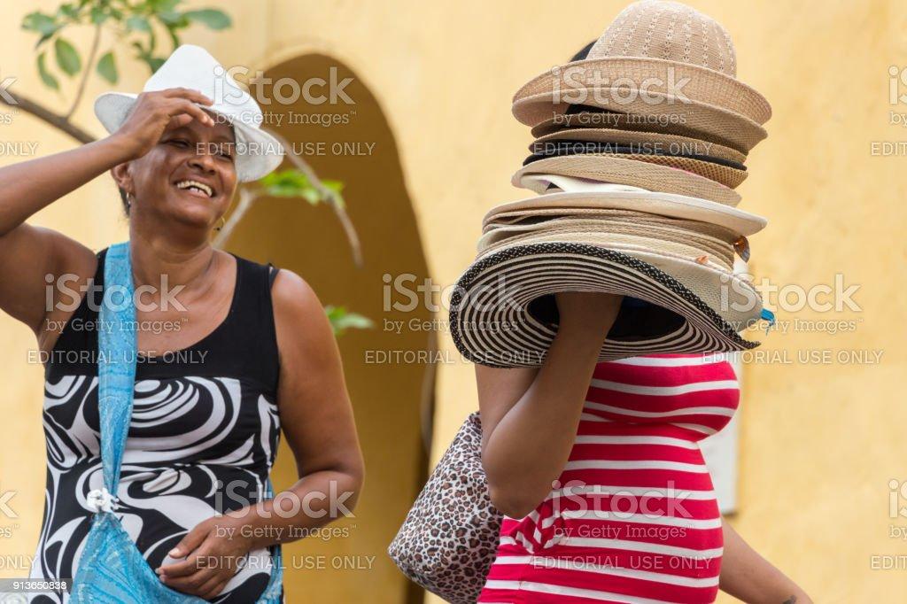 A hat vendor and a customer at La Puerta del Reloj in Cartagena. stock photo