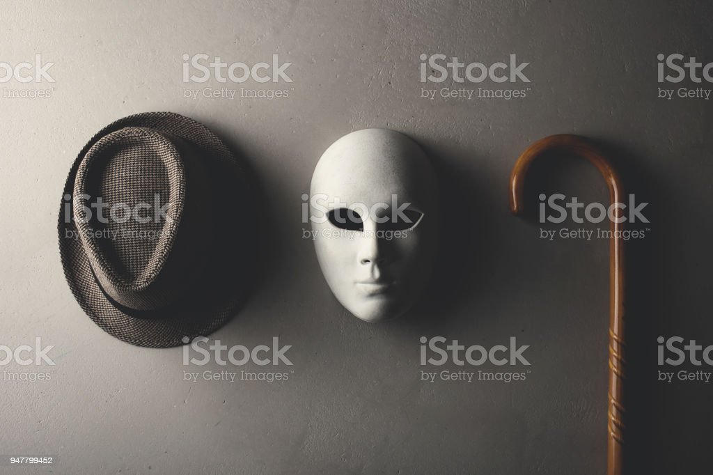 hat white mask and stick hanging on the wall stock photo