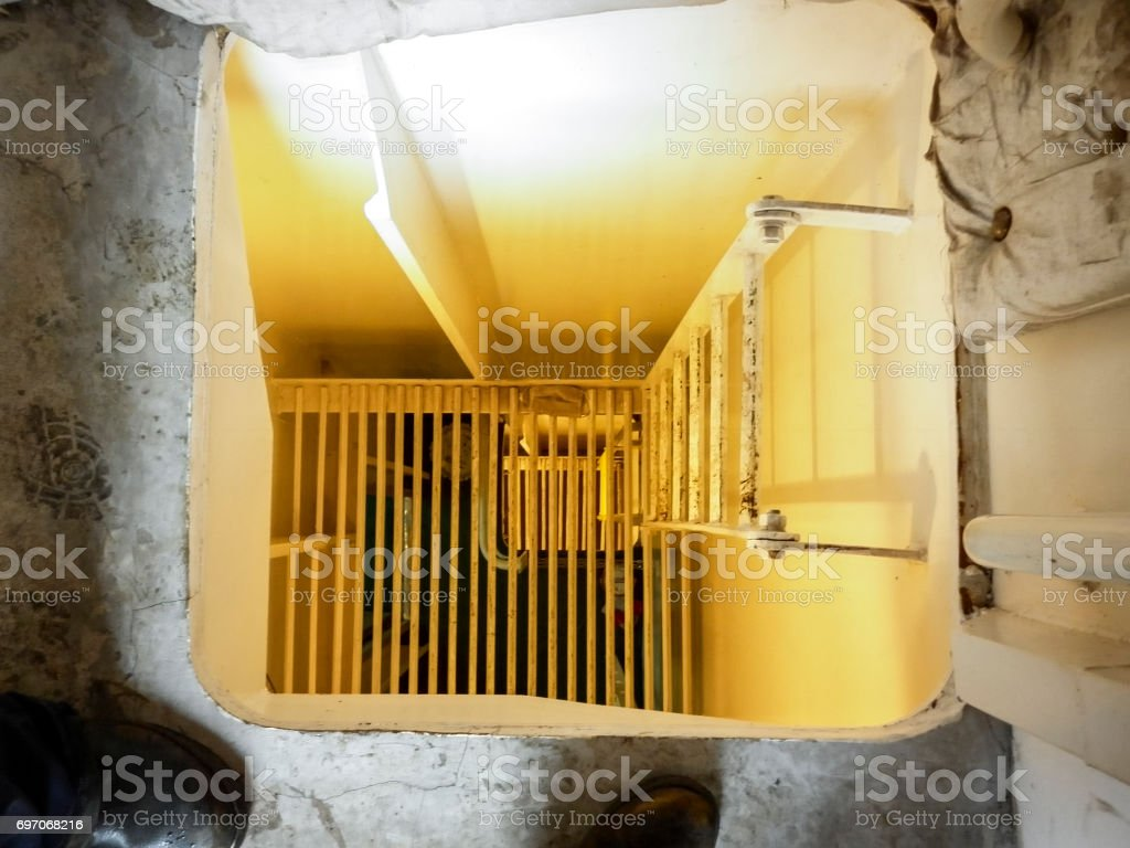 A hatch with a ladder to descend to the next level. stock photo