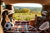 Photo of a family car ready for the summer holiday. The trunk of SUV packed for a weekend road trip. Photo of interior of open car trunk and garden. Soccer ball and picnic basket in a car trunk on a sunny day.