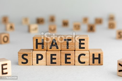Hate speech - words from wooden blocks with letters, speech that attacks a basis attributes such as race, religion, sexual orientation, or gender identity hate speech concept, random letters around, white  background