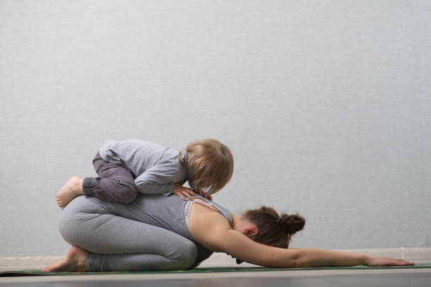 Hatha yoga fitness mother with baby stock photo
