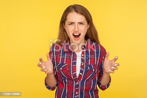 808681534 istock photo Hatred anger emotions. Portrait of crazy annoyed ginger girl in checkered shirt standing with raised hands and shouting madly 1206416680