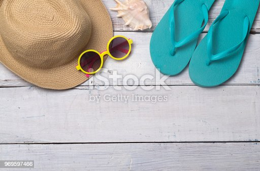 674650538istockphoto Hats, sunglasses, beach shoes, towels on the board 969597466