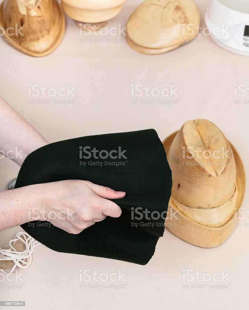 hatter preparing a felt hood for shaping stock photo