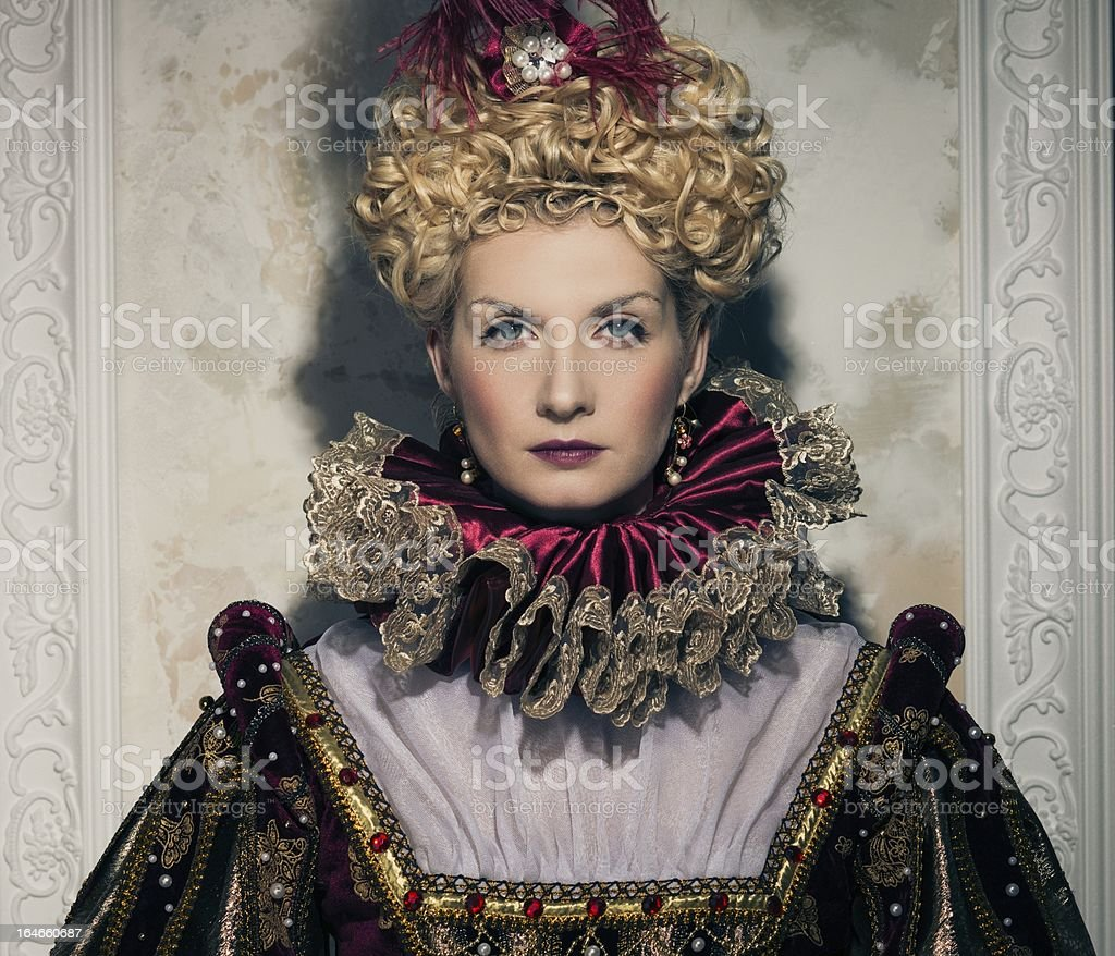 Haughty queen in royal dress stock photo