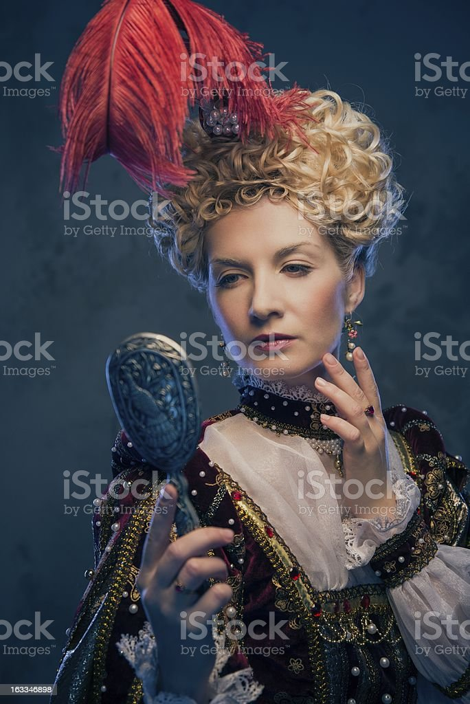 Haughty queen in royal dress with mirror royalty-free stock photo