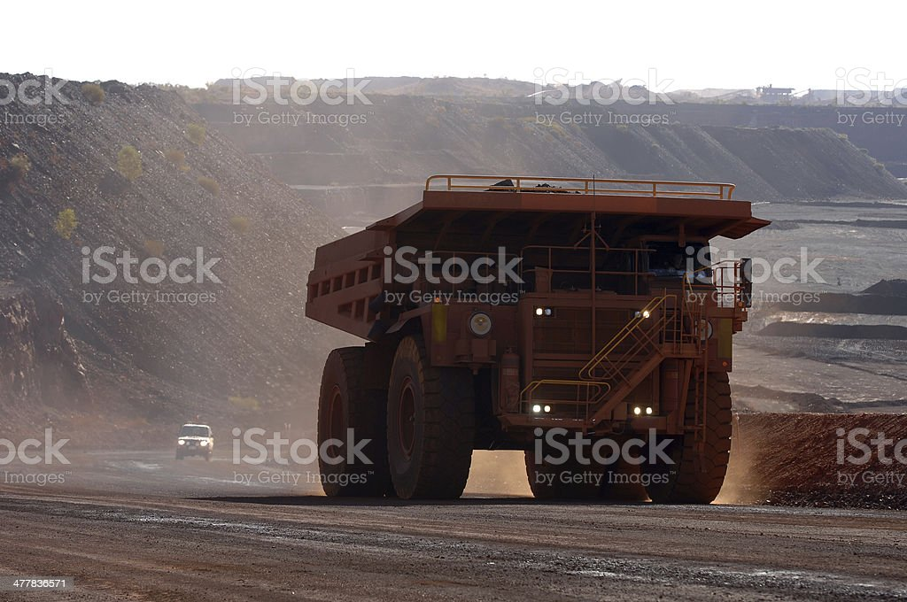 Haul truck followed by a small vehicle on a mine. stock photo