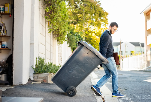 Man pulling a wheeled dumpster out of his garage while going to work