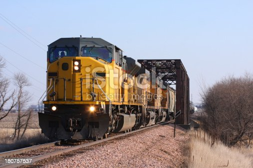 A set of yellow locomotives haul the freight across a bridge and onward northeast.