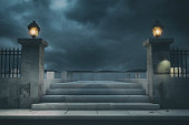 A haunted halloween cemetery background with dark stormy clouds at night with copy space.