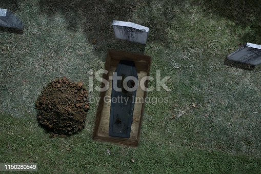 Aerial view of a freshly dug grave site on a haunted Halloween night.  The grave has been freshly dug with pile of dirt and casket.