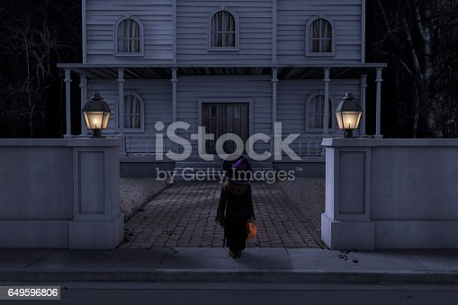 A female child trick or treater in a witch costume approaching a haunted mansion or house on halloween night with her jack-o-lantern full of candy.