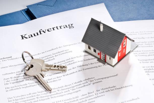 Haus mit Schlüssel und Kaufvertrag stock photo