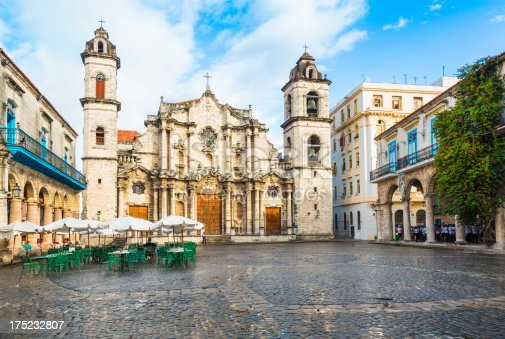 The large Cathedral of Havana in Cuba sits in an empty square.  Unused tables with umbrellas and a tree are in the square during this partially cloudy day.
