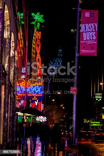 New York City, NY, USA - March 10, 2015: Neon sign view of Havana Central Restaurant and Bar in Times Square. Jersey Boys banner on pole. Young men on street. Light rain.