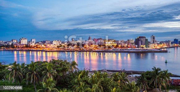 Havana city by sea against sky at blue hour. Cuba