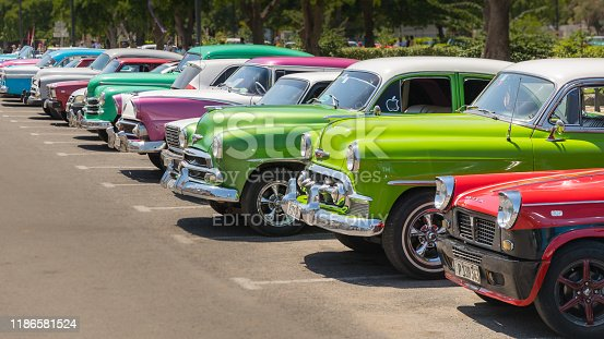 Havana, Cuba - July 23, 2018; A row of typical colorful Cuban oldtimer classic cars standing in line during day time on a parking lot