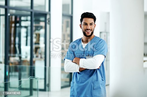 Shot of a young medical practitioner standing with his arms crossed in a hospital