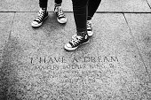Washington DC, USA - June 2017: Youth in their sneakers standing by the marker engraving memorializing the location of where Martin Luther King made his famous \