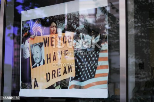 Washington, USA - July 8, 2011: The reflaction of demonstrators on a window shop. Woman carrying a pancart with the image of Dr. King and the slogan