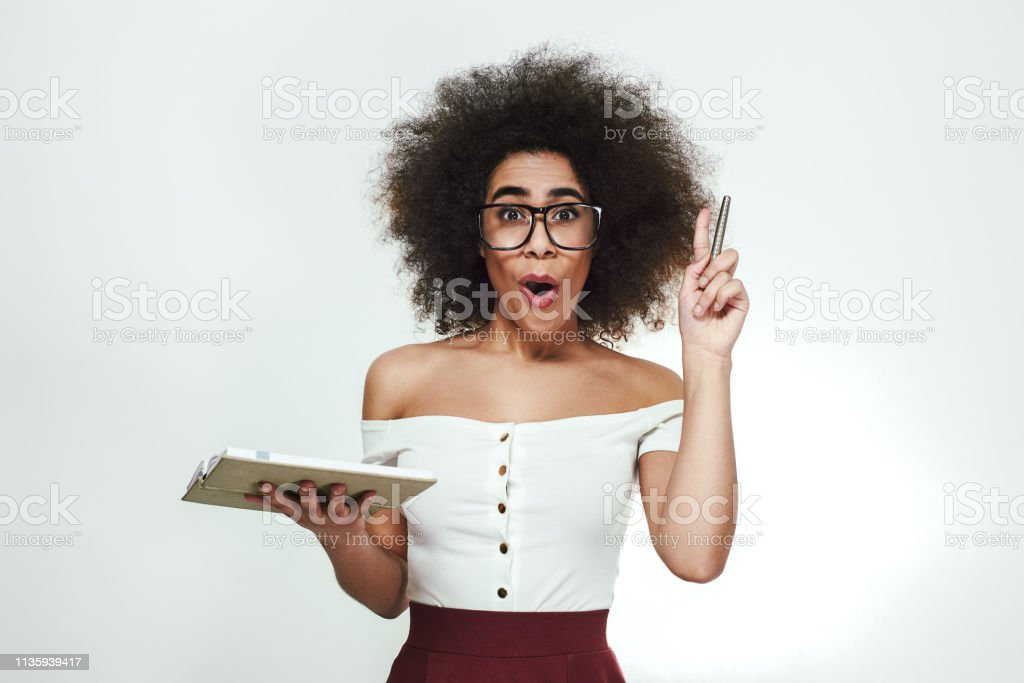 I have a great idea! Stusio portrait of excitedd and smart african girl in eyewear holding a notebook and pointing finger up with opened mouth stock photo