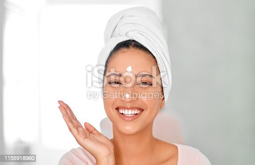 Shot of an attractive young woman applying moisturizer on her face in her bathroom at home