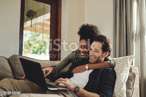 Shot of a happy young couple using a laptop while relaxing on a couch in their living room at home