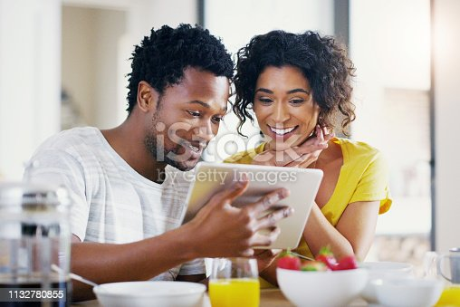 Shot of a young couple using a digital tablet together while having breakfast at home